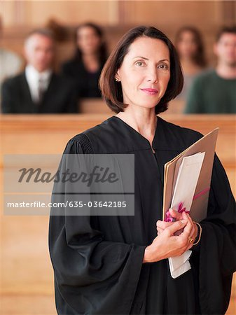 Confident judge holding file in courtroom Stock Photo - Premium Royalty-Free, Image code: 635-03642185