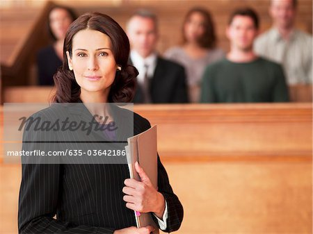 Smiling lawyer holding file in courtroom Stock Photo - Premium Royalty-Free, Image code: 635-03642186