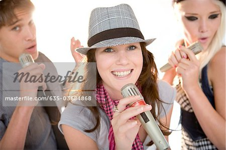 Friends singing in band together Stock Photo - Premium Royalty-Free, Image code: 635-03684868