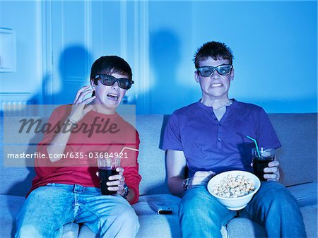 Teenage boys with snacks watching television with 3-D glasses Stock Photo - Premium Royalty-Free, Image code: 635-03684921