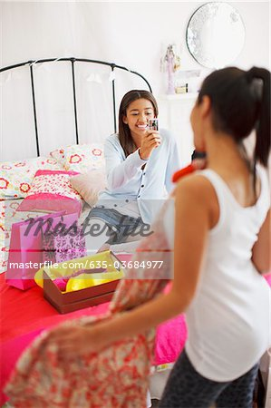Teenage girl taking photograph of friend's dress Stock Photo - Premium Royalty-Free, Image code: 635-03684977