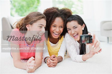 Laughing teenage girls taking self-portrait Stock Photo - Premium Royalty-Free, Image code: 635-03685014