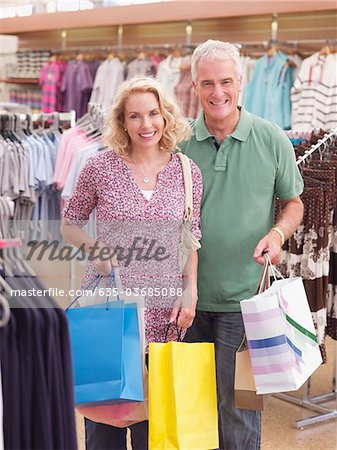 Couple carrying shopping bags in store Stock Photo - Premium Royalty-Free, Image code: 635-03685088