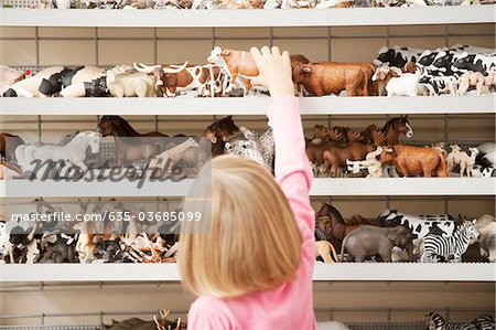 Girl reaching for plastic cow in toy store Stock Photo - Premium Royalty-Free, Image code: 635-03685099