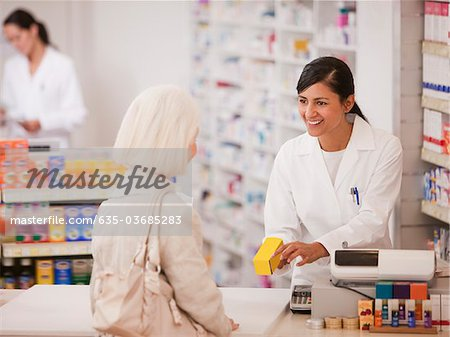 Pharmacist handing medication to customer in drug store Stock Photo - Premium Royalty-Free, Image code: 635-03685283