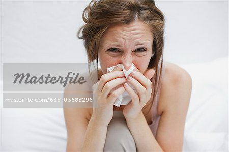 Sick woman in bed blowing nose Stock Photo - Premium Royalty-Free, Image code: 635-03685296