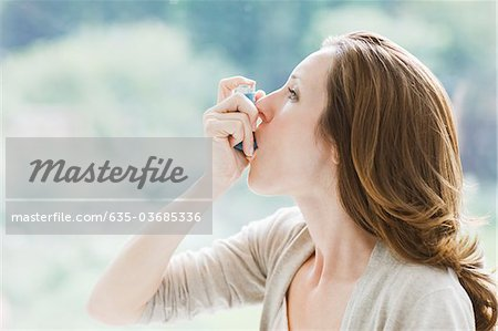 Woman using asthma inhaler Stock Photo - Premium Royalty-Free, Image code: 635-03685336