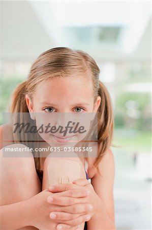 Smiling girl with bandage on knee Stock Photo - Premium Royalty-Free, Image code: 635-03685345