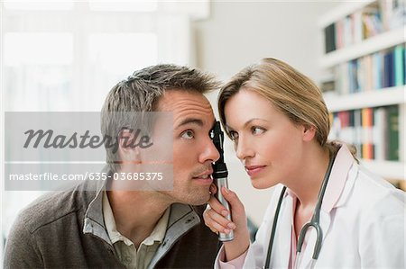 Doctor examining patient's eye in doctor's office Stock Photo - Premium Royalty-Free, Image code: 635-03685375