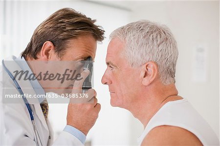 Doctor examining patient's eye in doctor's office Stock Photo - Premium Royalty-Free, Image code: 635-03685376