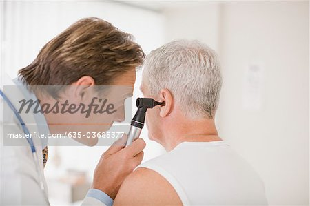 Doctor examining patient's ear in doctor's office Stock Photo - Premium Royalty-Free, Image code: 635-03685377