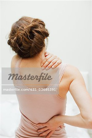 Woman rubbing aching back Stock Photo - Premium Royalty-Free, Image code: 635-03685391