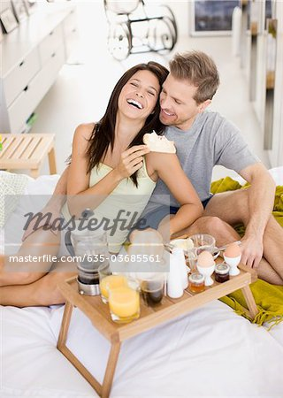 Happy couple having breakfast in bed Stock Photo - Premium Royalty-Free, Image code: 635-03685561