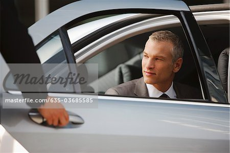 Chauffeur opening car door for businessman Stock Photo - Premium Royalty-Free, Image code: 635-03685585