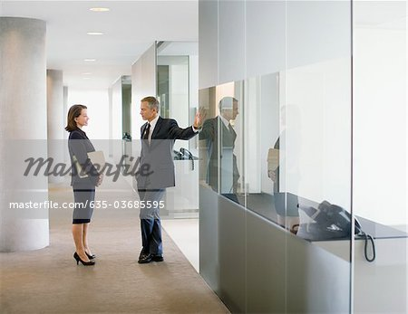 Business people talking in modern office corridor Stock Photo - Premium Royalty-Free, Image code: 635-03685595