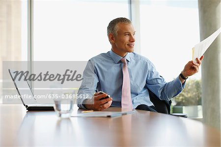 Businessman holding paperwork at desk Stock Photo - Premium Royalty-Free, Image code: 635-03685612