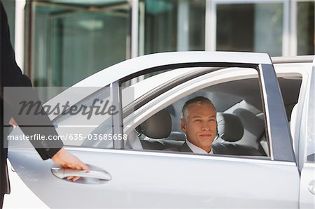 Chauffeur opening car door for businessman Stock Photo - Premium Royalty-Free, Image code: 635-03685658