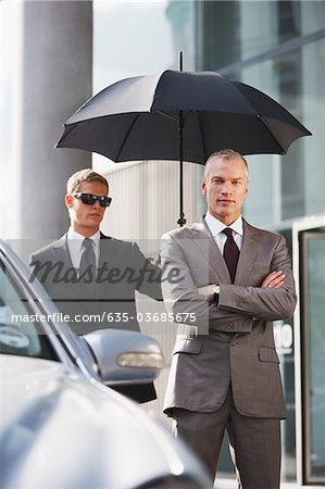 Chauffeur holding umbrella for businessman Stock Photo - Premium Royalty-Free, Image code: 635-03685675