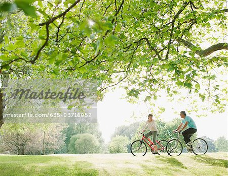 Couple riding bicycles underneath tree Stock Photo - Premium Royalty-Free, Image code: 635-03716052