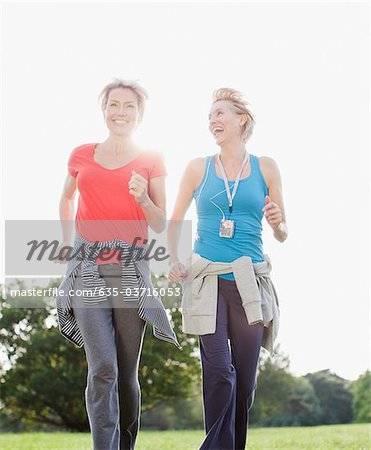 Smiling women jogging together Stock Photo - Premium Royalty-Free, Image code: 635-03716053