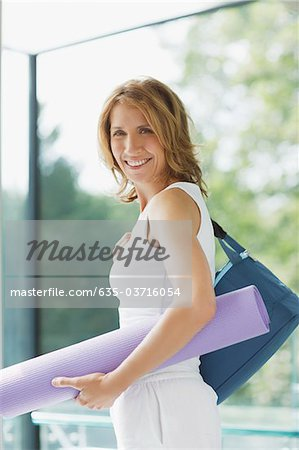 Smiling woman holding yoga mat Stock Photo - Premium Royalty-Free, Image code: 635-03716054