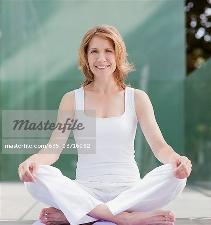 Smiling woman practicing yoga Stock Photo - Premium Royalty-Free, Image code: 635-03716062
