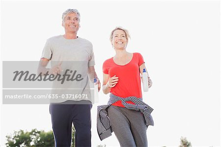 Couple with water bottles jogging together Stock Photo - Premium Royalty-Free, Image code: 635-03716071