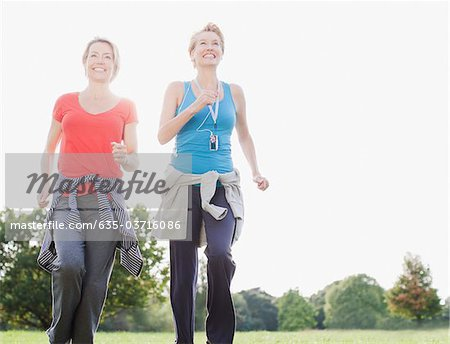 Smiling women jogging together Stock Photo - Premium Royalty-Free, Image code: 635-03716086