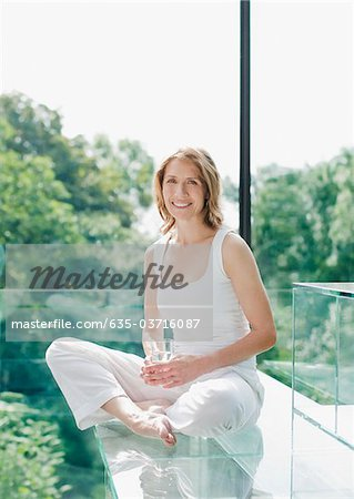 Smiling woman sitting on floor drinking water Stock Photo - Premium Royalty-Free, Image code: 635-03716087