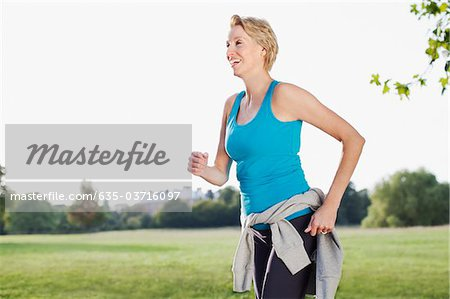 Smiling woman jogging in park Stock Photo - Premium Royalty-Free, Image code: 635-03716097