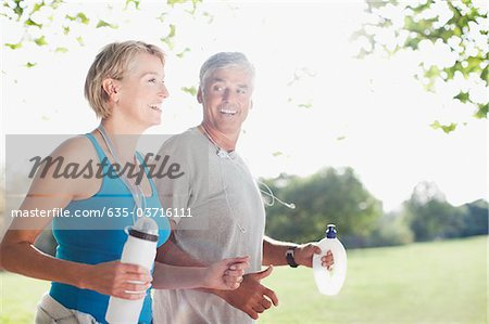 Couple jogging together with water bottles Stock Photo - Premium Royalty-Free, Image code: 635-03716111