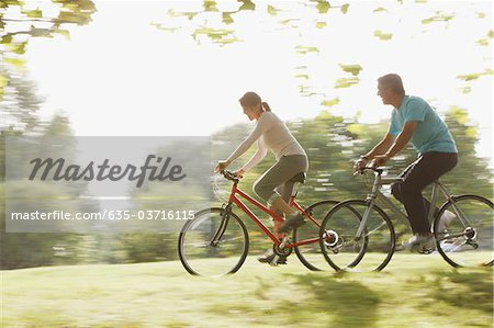 Couple riding bicycles together Stock Photo - Premium Royalty-Free, Image code: 635-03716115