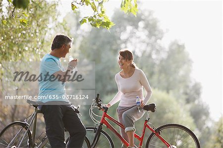 Couple with bicycles drinking water Stock Photo - Premium Royalty-Free, Image code: 635-03716124