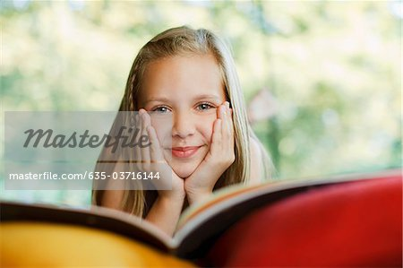Smiling girl reading book Stock Photo - Premium Royalty-Free, Image code: 635-03716144