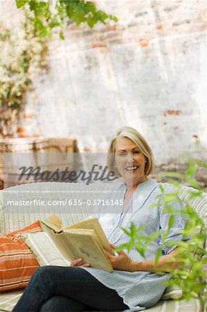 Smiling woman reading book on patio Stock Photo - Premium Royalty-Free, Image code: 635-03716145