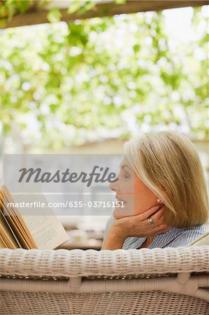 Woman reading book on patio Stock Photo - Premium Royalty-Free, Image code: 635-03716151