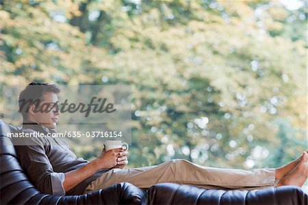 Man reclining in chair drinking coffee Stock Photo - Premium Royalty-Free, Image code: 635-03716154