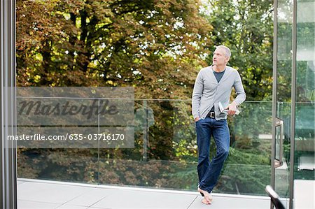 Man standing on balcony with book Stock Photo - Premium Royalty-Free, Image code: 635-03716170