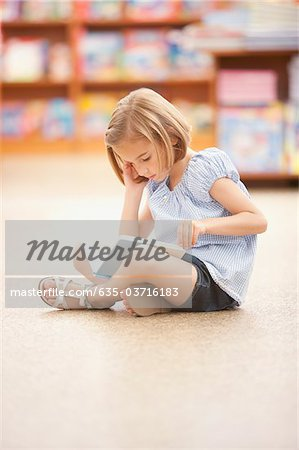 Girl sitting on floor reading book Stock Photo - Premium Royalty-Free, Image code: 635-03716183