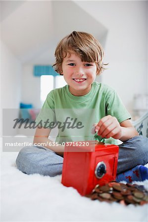 Boy putting coins into safe piggy bank Stock Photo - Premium Royalty-Free, Image code: 635-03716220