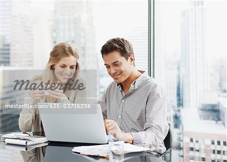 Business people using laptop together Stock Photo - Premium Royalty-Free, Image code: 635-03716236