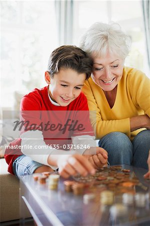 Grandmother and grandson counting coins Stock Photo - Premium Royalty-Free, Image code: 635-03716246