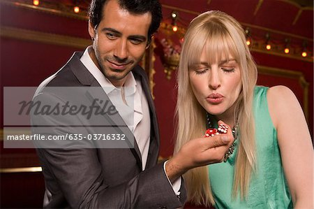 Girlfriend blowing on boyfriend's dice in casino Stock Photo - Premium Royalty-Free, Image code: 635-03716332