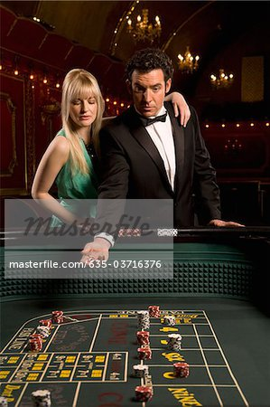 Girlfriend watching boyfriend throwing dice at craps table Stock Photo - Premium Royalty-Free, Image code: 635-03716376