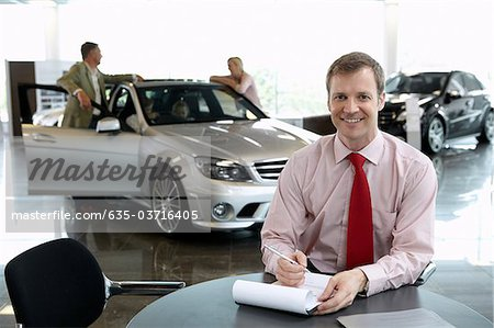 Salesman in automobile showroom