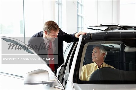 Salesman talking to man in new car in showroom Stock Photo - Premium Royalty-Free, Image code: 635-03716412