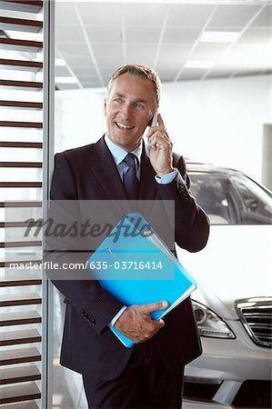 Salesman holding binder and talking on cell phone in automobile showroom Stock Photo - Premium Royalty-Free, Image code: 635-03716414
