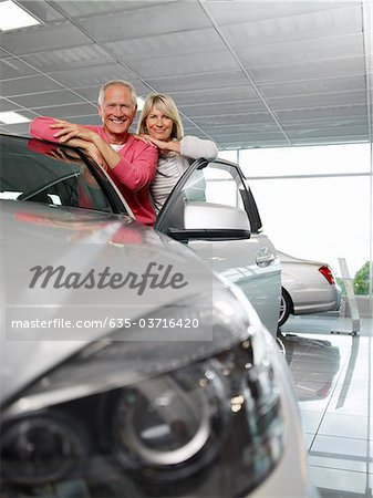 Couple looking at new car in showroom Stock Photo - Premium Royalty-Free, Image code: 635-03716420