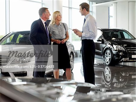 Salesman talking to couple in automobile showroom Stock Photo - Premium Royalty-Free, Image code: 635-03716423