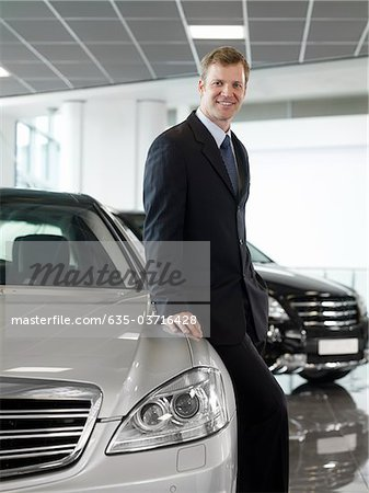 Salesman leaning on car in automobile showroom Stock Photo - Premium Royalty-Free, Image code: 635-03716428